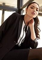 Modelo femenina con conjunto de falda y saco negros, formales, y blusa blanca con detalles negros debajo. Pulsa aquí para ver más ropa ejecutiva para mujer, abre en pestaña nueva.